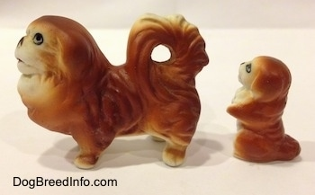 The left side of a brown with white Pekingese figurine and behind it is a brown with white Pekingese puppy in a begging pose figurine. The figurines have painted faces.