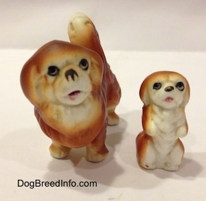 A brown with white Pekingese puppy figurine that is in a begging pose and to the left of it is a brown with white Pekingese figurine. The figurines mouthes are open.