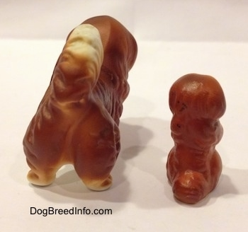The back of a figurine of a Pekingese puppy in a begging pose and a figurine of a brown with white Pekingese figurine. The tails of the figurines are arched up on each others back.