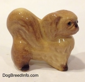 The right side of a tan with brown figurine of a Pekingese. The figurine has black paws.