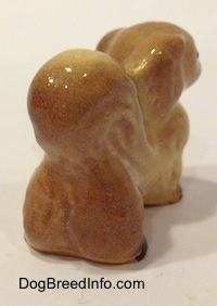 The back right side of a figurine of a tan with brown Pekingese. The tail of the figurine is arched onto its back.