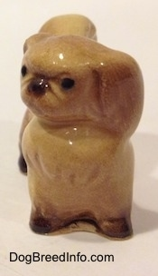 A figurine of a tan with brown Pekingese. The figurine turned its head to the left.