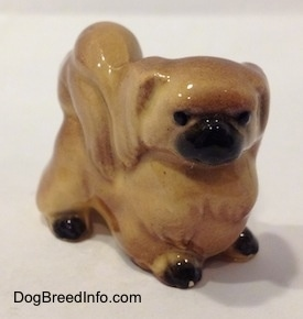 The front right side of a tan with brown Pekingese figurine. The figurine has black circles for eyes.