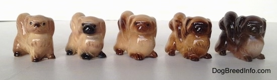 A line-up of different color variations of a Pekingese figurine. The figurines have black circles for eyes.