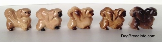 The right side of a line-up of different color variations of a Pekingese figurine. The tails of the figurines are arched across there backs.