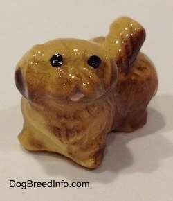 The front left side of a brown and tan figurine of a Pekingese puppy. The figurine has black circles for eyes.