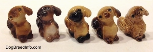 The front right side of five different color variations of a figurine of a Pekingese puppy seated figurine. The figurines have black circles for eyes.