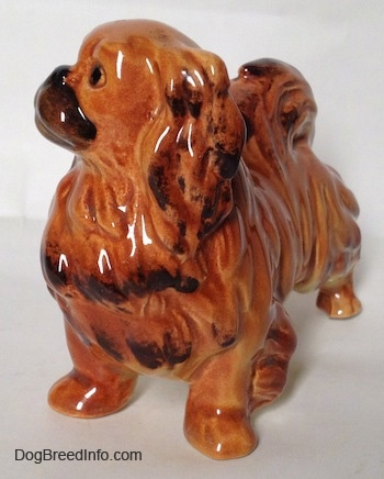 The front left side of a brown and tan with black Pekingese figurine. The figurine has black tipped ears.