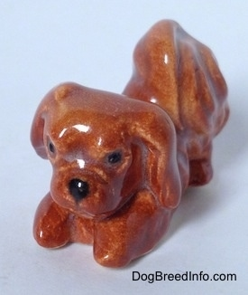 The front left side of a figurine of a brown Pekingese that is in a play bow pose. The figurine has black circles for eyes.