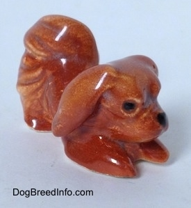 The front right side of a brown figurine of a Pekingese that is in a play bow pose. The figurine is glossy.