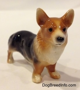 The front left side of a figurine that is a black and tan Pembrokw Welsh Corgi. This figurine has black circles for eyes.
