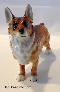 A brown with white and black porcelain Pembroke Welsh Corgi figurine. The figurine has a detailed face with a black  nose, black eyes a white chest going up to the chin and a black painted line for a mouth.