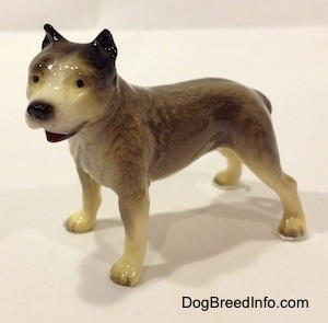 A figurine of a grey, black and white Pit Bull Terrier figurine. The figurine has black circles for eyes.