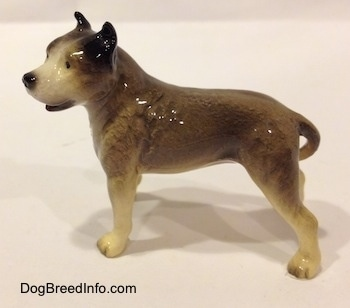 The left side of a grey, black and white Pit Bull Terrier figurine. The figurine has long legs.