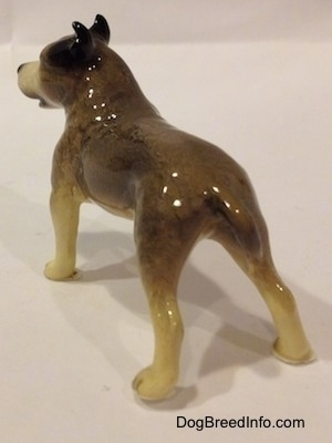 The back left side of a figurine of a black, gray and white Pit Bull Terrier figurine. The figurine has a small gray tail.