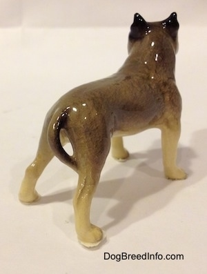 The back right side of a black, gray and white figurine of a Pit Bull Terrier. The figurine is glossy.