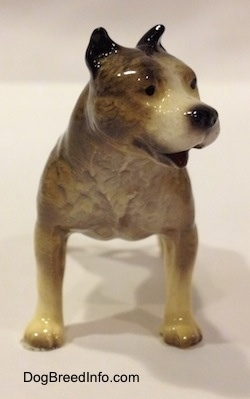 A black, gray and white Pit Bull Terrier figurine. The figurine has its mouth open.