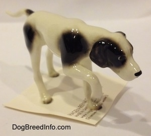 The front right side of a white with black spotted figurine of a Pointer in a pointing pose. The figurine has long legs.