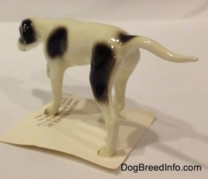 The back left side of a white with black Pointer in a pointing pose figurine. The figurine has a black spot at the base of its tail.