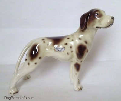 The right side of a white and tan Pointer with brown patches figurine. There is a silver sticker on the side and it has the word Pointer on it.
