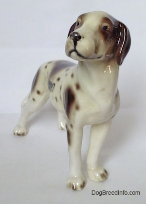 The front right side of a figurine of a white and tan Pointer with brown patches. The figurine has black circles for eyes.