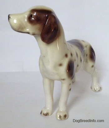 The front left side of a white and tan figurine of a Pointer with brown patches. The figurine has long brown ears.