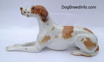 The left side of a porcelain figurine of a white with brown Pointer in a lying pose. The figurine has long legs.