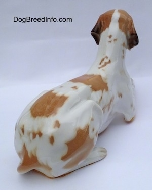 The back right side of a porcelain white with brown figurine of a Pointer in a lying pose. The figurine has a long tail along its left side.