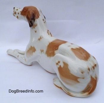 The back left side of a porcelain white with brown Pointer in a lying pose figurine. The tips of the figurines ears are black.