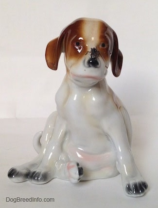 A figurine of a Pointer puppy sitting with a fly on its nose figurine. The figurine has black circles for eyes.