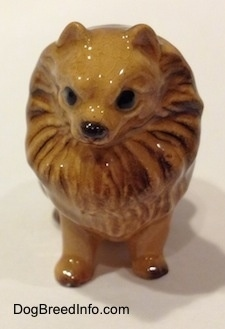 A figurine of a brown Pomeranian sitting. The figurine has hair around its head like a lions mane.