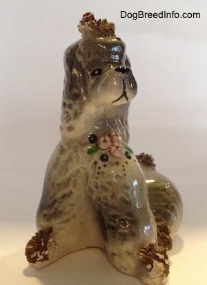 A ceramic spaghetti Poodle figurine. The figurine hhas flowers on it and it is in a sitting position.