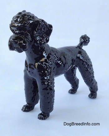The front left side of a figurine of a black Poodle. The figurine has fine hair details.