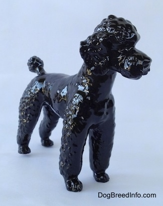 The front right side of a black Poodle standing figurine. Its hard to differentiate the ears from the body of the figurine.