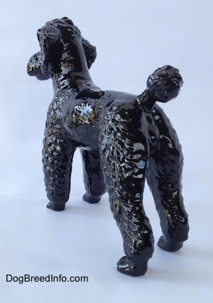The back left side of a figurine of a black Poodle standing.