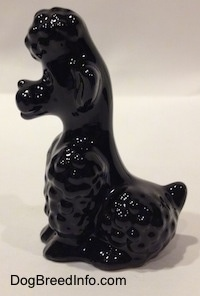 The left side of a figurine of a sitting black Poodle. The figurine has short legs.