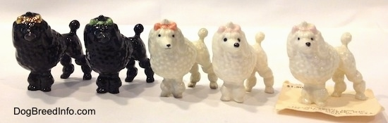 A line-up of five different color variations of a Poodle with a bow in its hair figurine.