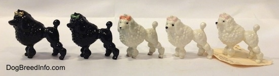 The left side of five different color variations of a figurine of a Poodle wth a bow in its hair. The figurines have black circles for eyes.