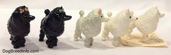 Five different color variations of a figurine of a Poodle with a bow in its hair. The figurines have a large poof of hair on its upper body.