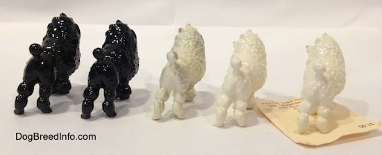The back right side of five different color variations of a Poodle with a bow in its hair figurine. The figurine has a short tail with a larg poof at the end.