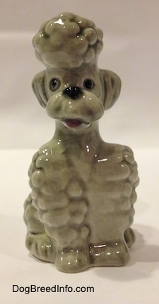 A gray Poodle sitting figurine. The figurine has its mouth open.