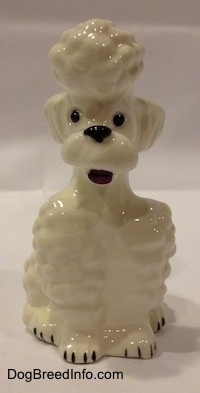 A white Poodle in a sitting pose figurine. The figurine has its mouth open.