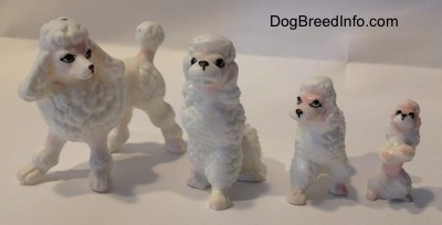 A white with pink bone china Poodle family. There are two adult figurines and two puppy figurines.