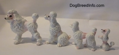 The left side of a bone china family of Poodle figurines. The ears are hard to differentiate from the body of the figurines.