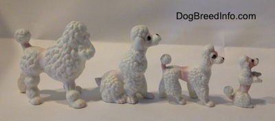 The right side of a family of four bone china Poodle puppy figurines. The figurines have black circles for eyes.