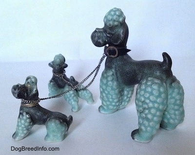 The left side of three Porcelain Poodle figurines that are chained together. All of the Poodles have a hair poof on there heads.
