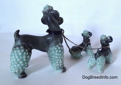 The right side of three porcelain figurines of Poodles chained together. All of the figurines tails are arched upwards in the air.