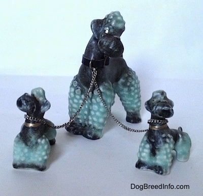 Three black with green Porcelain Poodles chained together figurines. The biggest figurine has a black leather collar on.