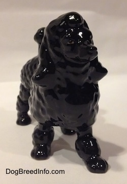 A black porcelain Poodle figurine. It is hard to see the features on the figurines face.