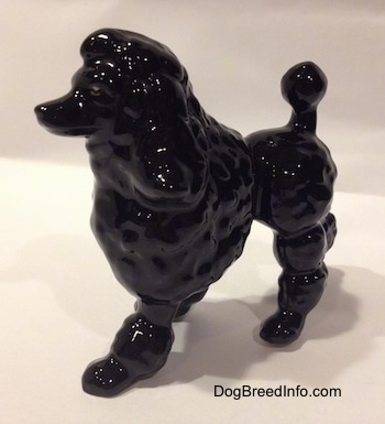 The front left side of a black porcelain figurine of a Poodle. The figurine has long legs.